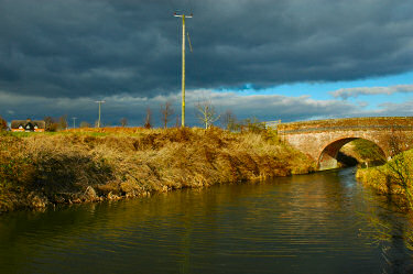 Picture of a bridge over a canal with dramatic clouds overhead