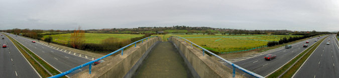 Picture of a panoramic view over a motorway and towards houses on a low hill