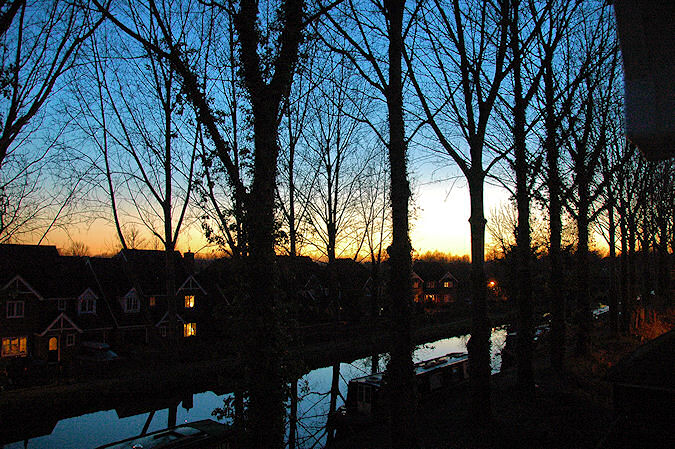 Picture of a sunset over a canal lined with trees, after the sun has set and only the gloaming remains