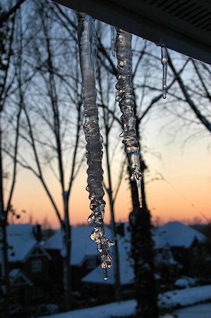 Picture of two icicles hanging from a roof, sunset in the background