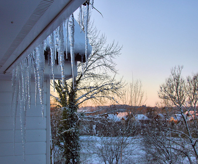 Picture of icicles hanging from a roof, a wintry landscape in the background