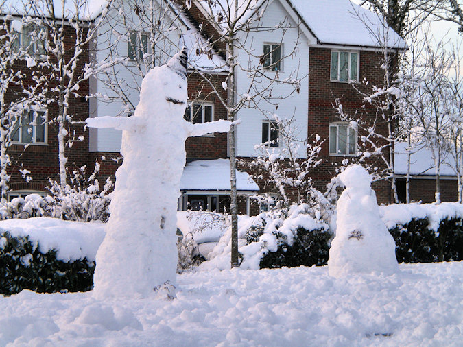 Picture of two snowmen, one large male and a smaller female